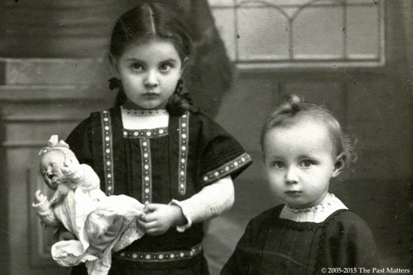 Children with a German bisque character doll and horse pull toy.