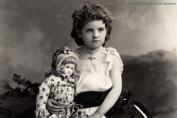 Young girl about 1886 with French bisque Jumeau doll.
