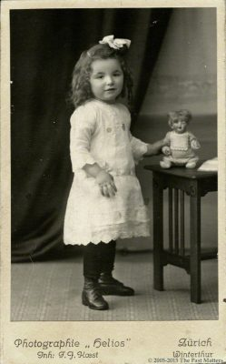 Young girl with German bisque character doll.