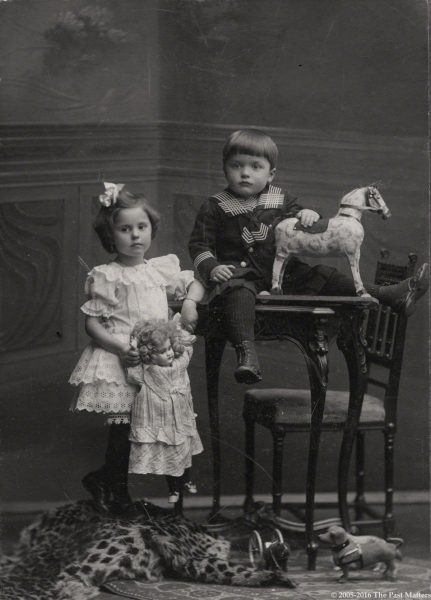 Children in 1909 with their toys, including a dachshund, horse, and German bisque doll.