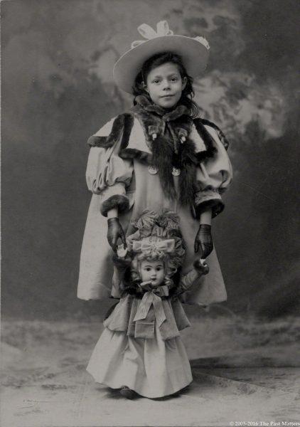 Anna H. Burdett with her large blonde German bisque doll in 1899