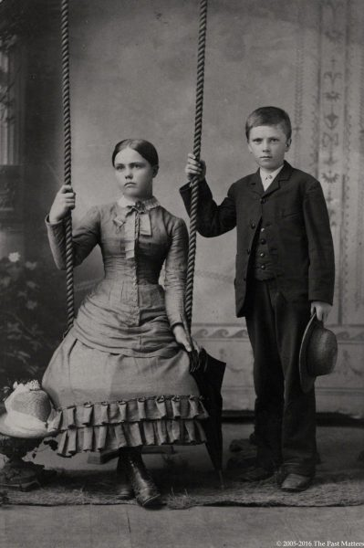 Two children, one on a swing, with their summer straw hats circa 1886