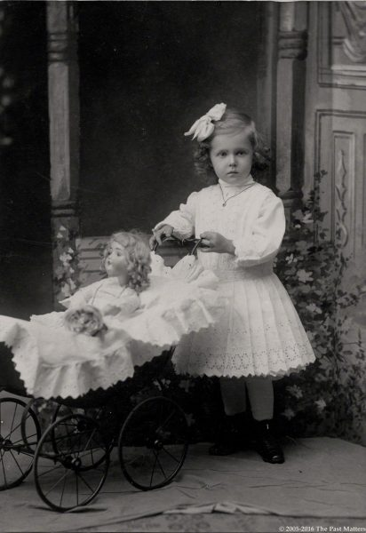 A young girl with her blonde German bisque doll in a carriage circa 1905