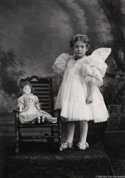 A young girl in a fairy costume with her German bisque doll circa 1895