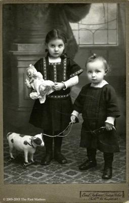 Children with German bisque character doll and horse pull toy
